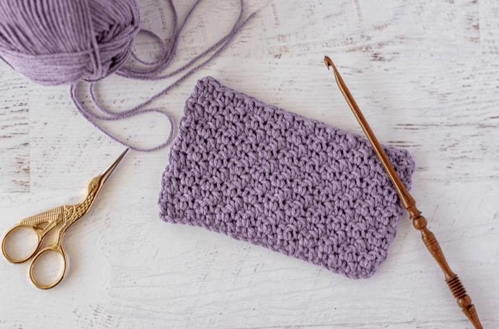 Crochet purple fabric with wood crochet hook and gold scissors