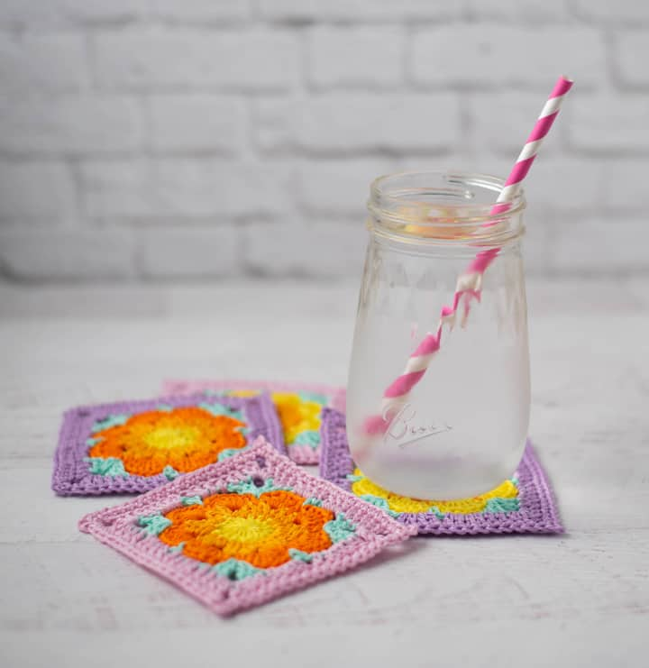 eau glacée sur violet, rose, Un verre d'eau avec une paille rose sur or et orange sous-verre de fleurs au crochet