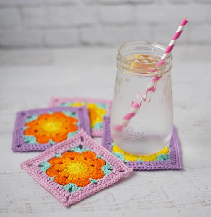 eau glacée sur violet, rose, Un verre d'eau sur des sous-verres de fleurs au crochet or et orange