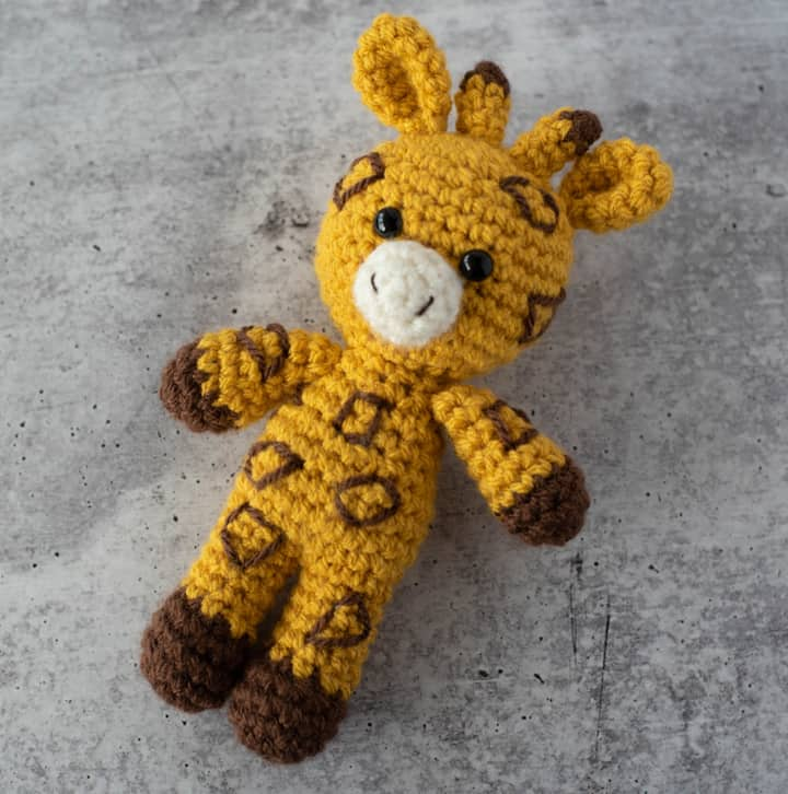 yellow and brown crochet stuffed giraffe on a gray cement background