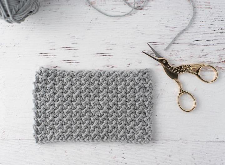 échantillon de crochet gris avec des ciseaux de cigogne