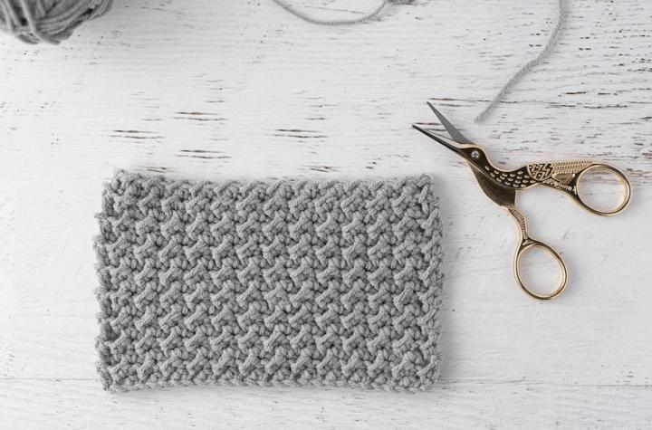 crochet stitch sample in gray yarn with stork scissors