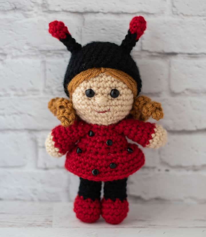 crochet doll with gold hair dressed up as a ladybug with a black hat