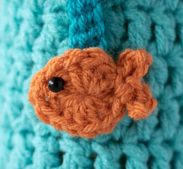 close up of orange crochet fish on blue crochet background