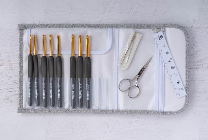 crochets gris en étui avec ciseaux, aiguilles et règle