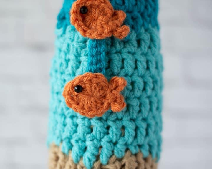 close up of orange fish on blue wine cozy