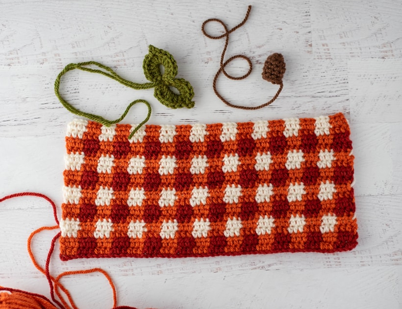 rectángulo a cuadros naranja de ganchillo, hojas verdes y tallo marrón