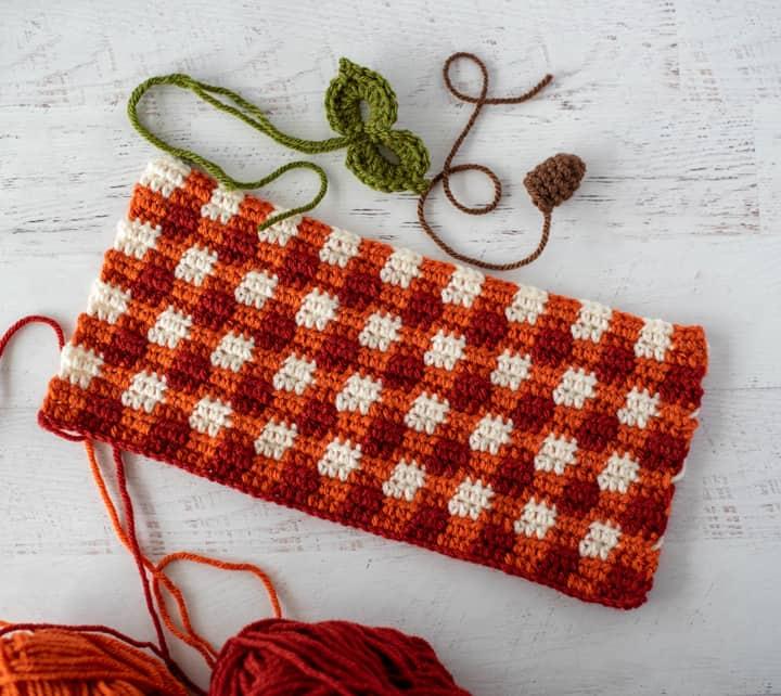 rectángulo a cuadros naranja de ganchillo, hojas verdes y vapor marrón