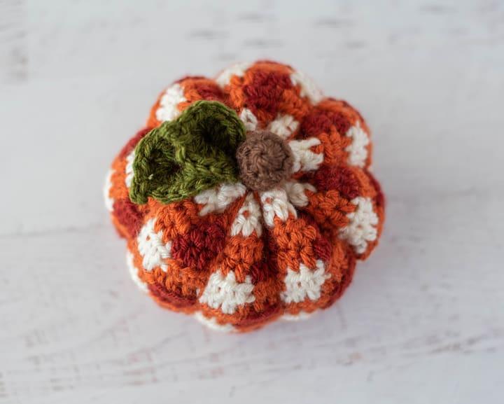 parte superior de calabaza naranja a cuadros de ganchillo con hojas verdes y tallo marrón