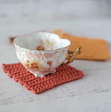 Coffee cup on rust color crochet coaster